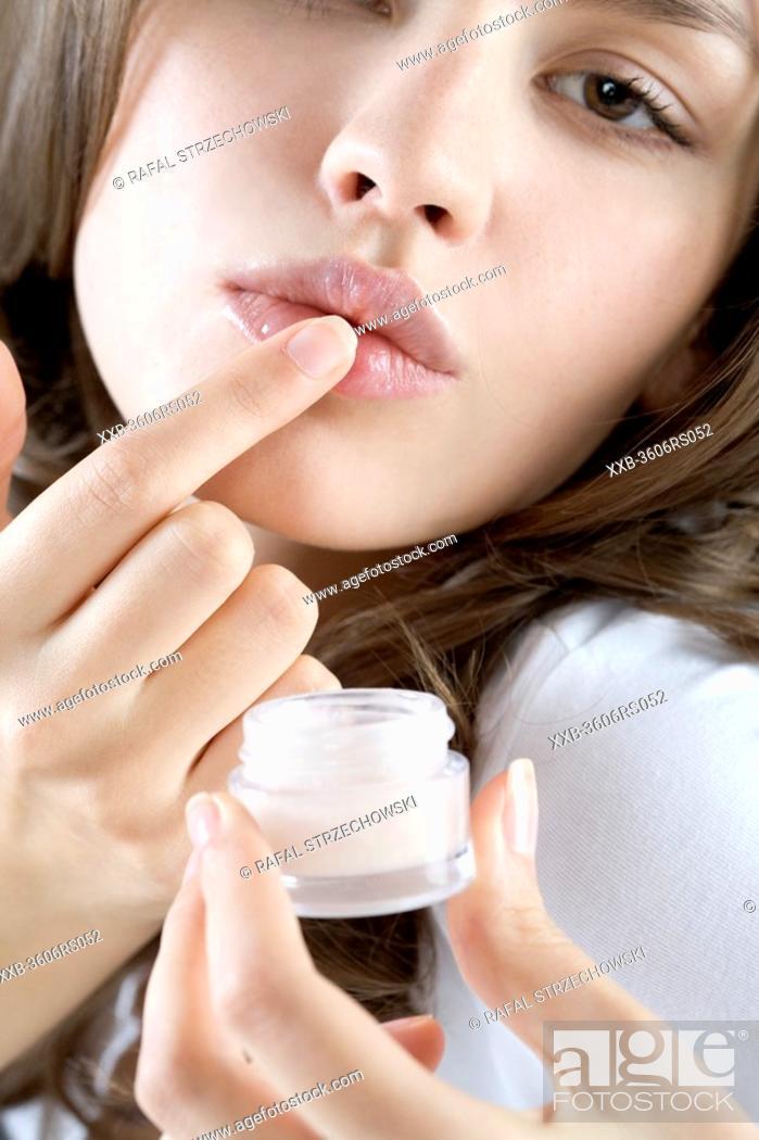 Stock Photo: young woman applying lipbalm.