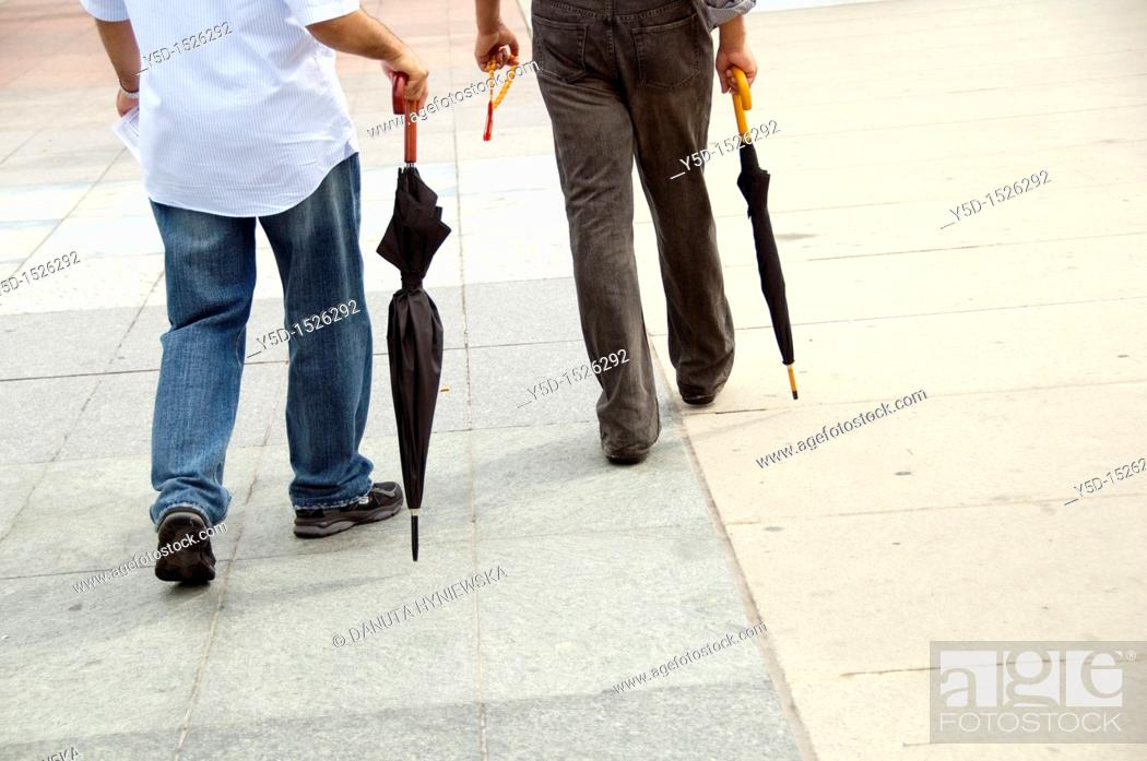 Stock Photo: better to be prepared, two men walking with closed umbrellas, streetlife.
