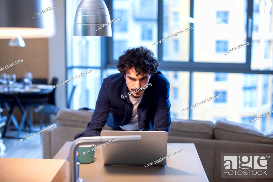 Stock Photo: Man with coffee working at laptop in apartment kitchen.