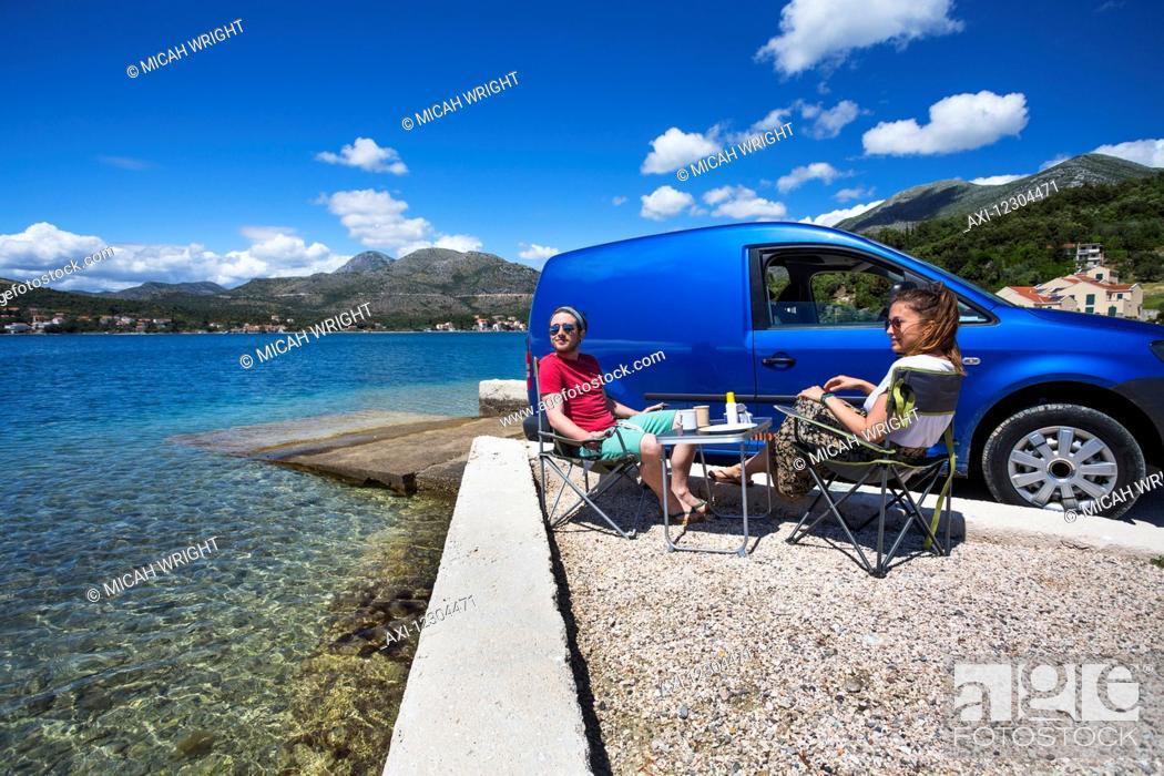 Imagen: A couple sits outside their camper van at a beach along the coast; Slano, Croatia.
