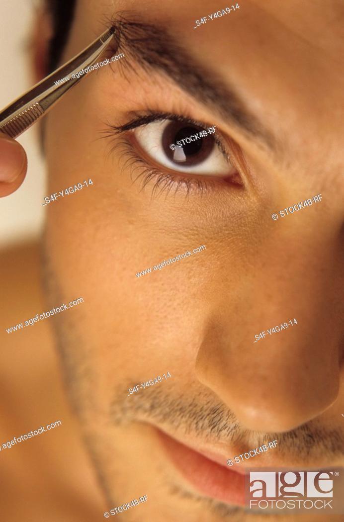 Stock Photo: Man plugging his Eyebrow with Tweezers - Vanity - Beauty.