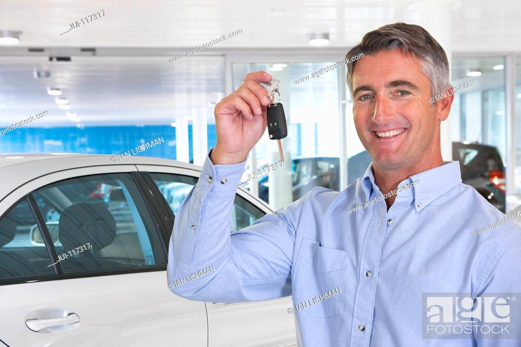 Stock Photo: Portrait Of Man Collecting New Car From Showroom.