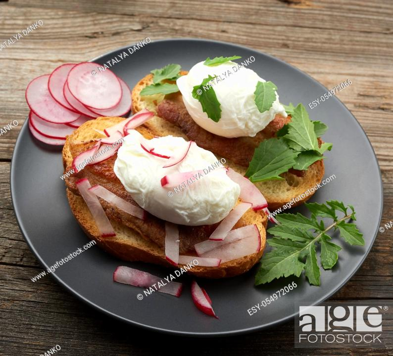Stock Photo: two sandwiches on a toasted white slice of bread with poached eggs, green leaves of arugula and radish in a round plate, top view.