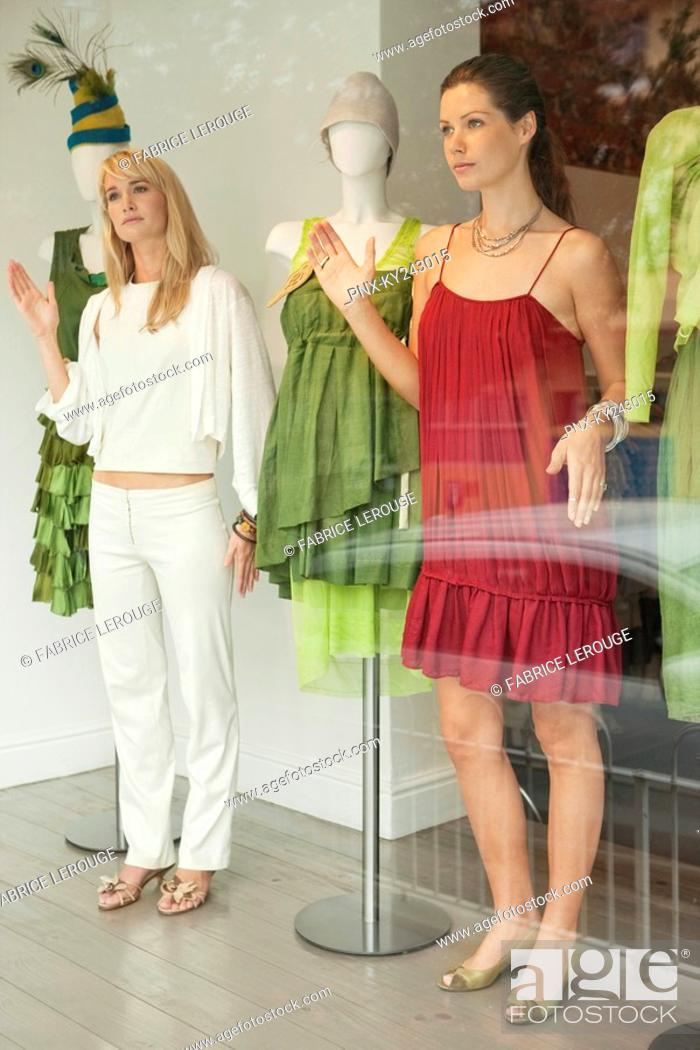 Stock Photo: Two women imitating a mannequin in a boutique.
