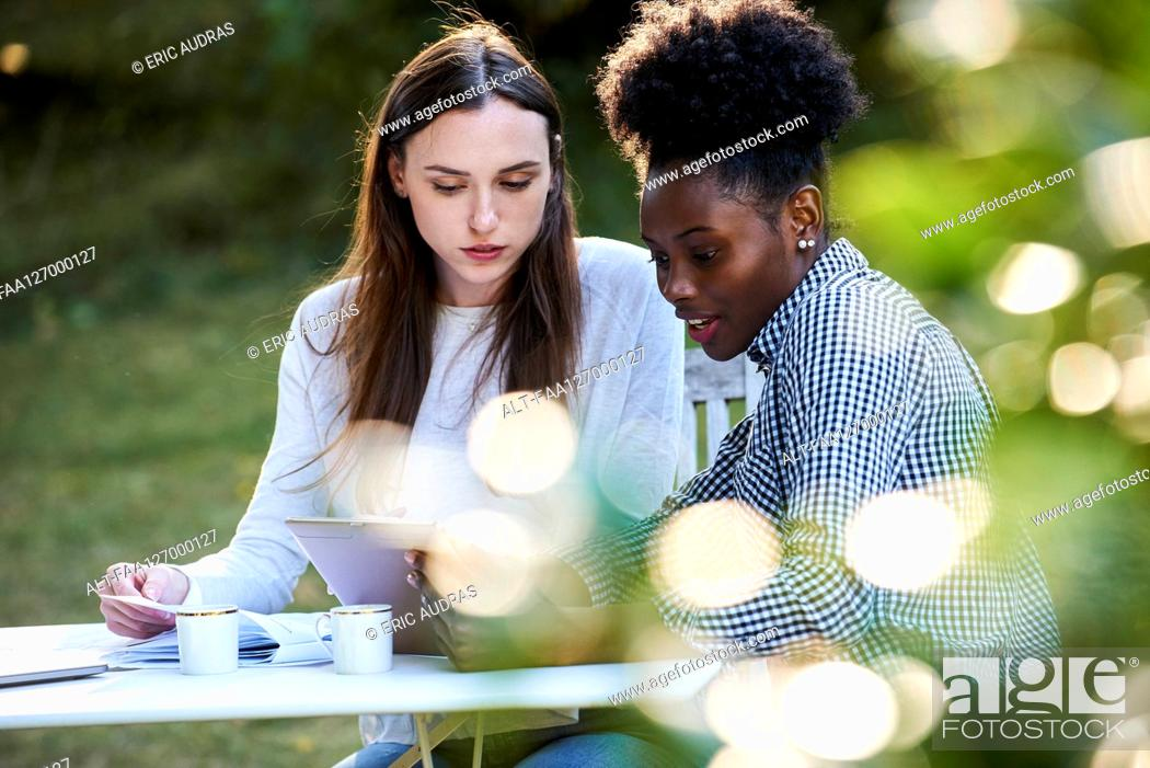 Photo de stock: Young female friends using digital tablet while studying in park.
