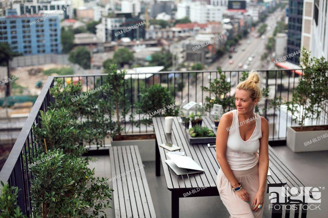 Imagen: Caucasian woman standing on balcony.