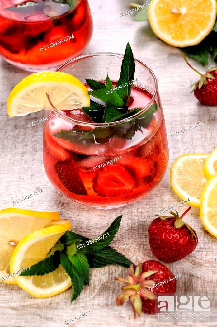 Stock Photo: A glass of chilled strawberry lemonade, mint leaves, a slice of lemon with ice.