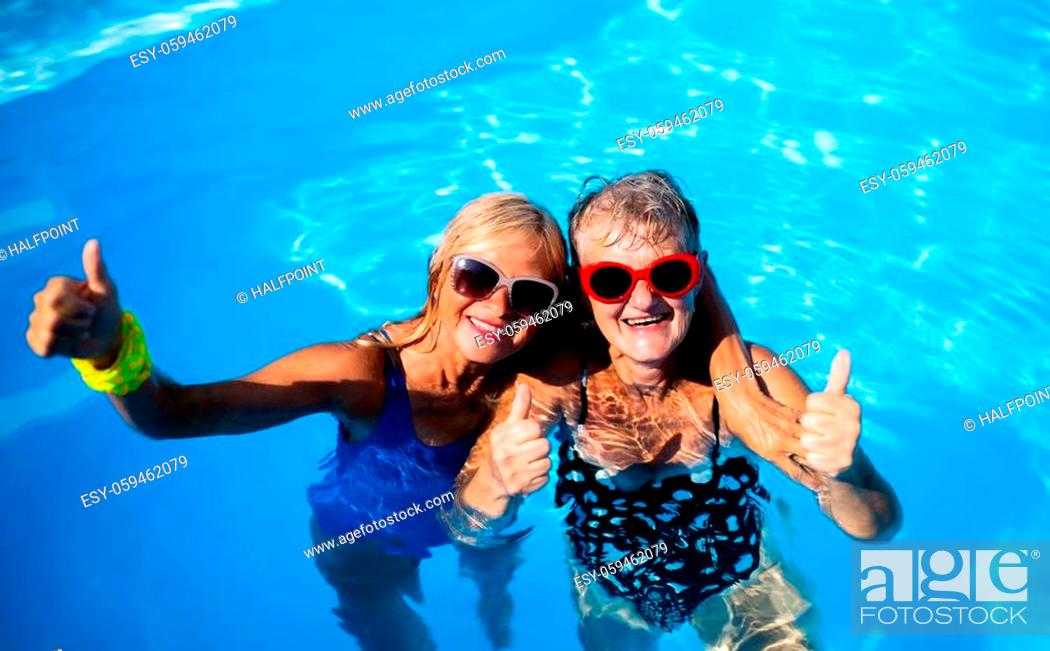Imagen: High angle view of cheerful senior women in swimming pool outdoors in backyard, looking at camera.
