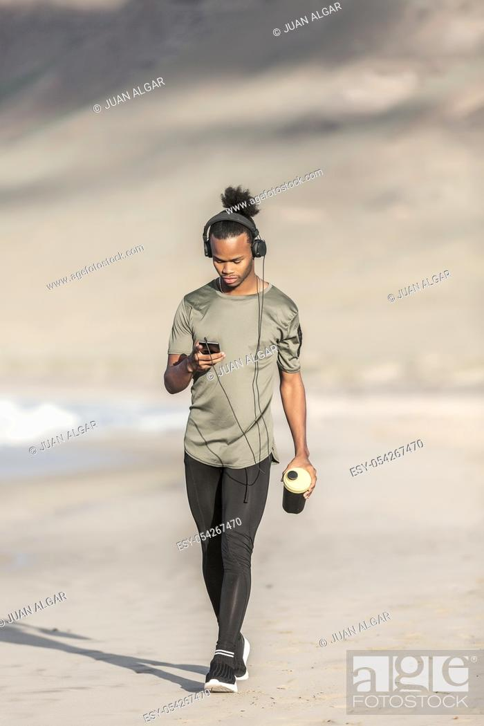Stock Photo: Attractive African American male with cup of hot drink listening to music and browsing smartphone while walking on sandy coast near sea.