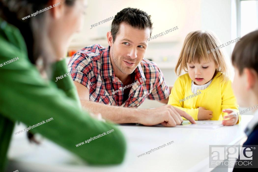Stock Photo: Couple teaching their children at home.