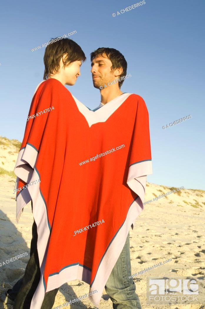 Stock Photo: Couple on the beach, sharing a poncho.