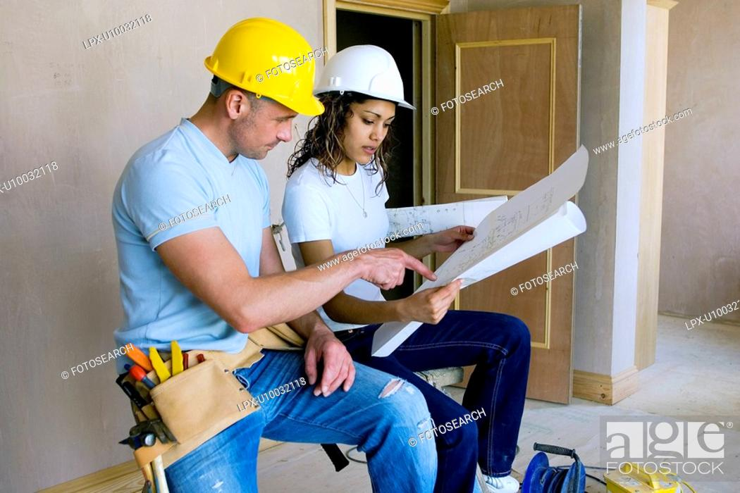 Stock Photo: Male builder with woman site manager reading plans.
