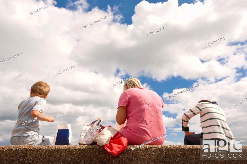 Stock Photo: Young family eat their fish and chips on the beach at Aldeburgh, Suffolk, England, Great Britain, Uk.