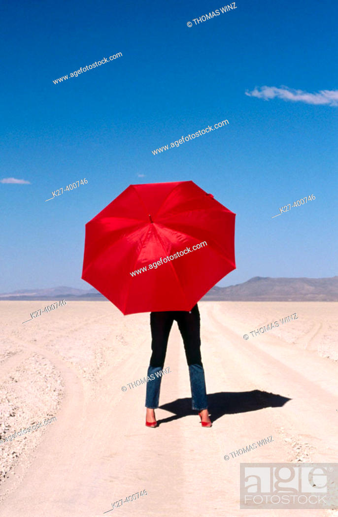 Stock Photo: Woman with red umbrella in the Black Rock Desert. Nevada. USA.