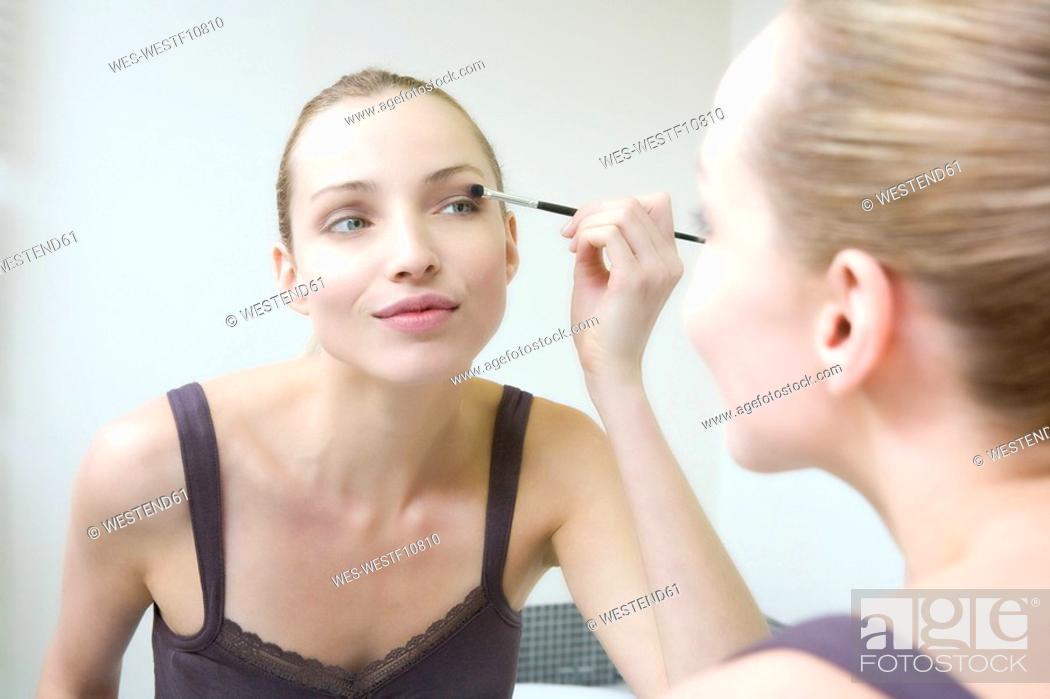 Stock Photo: Young woman applying eye shadow, portrait.