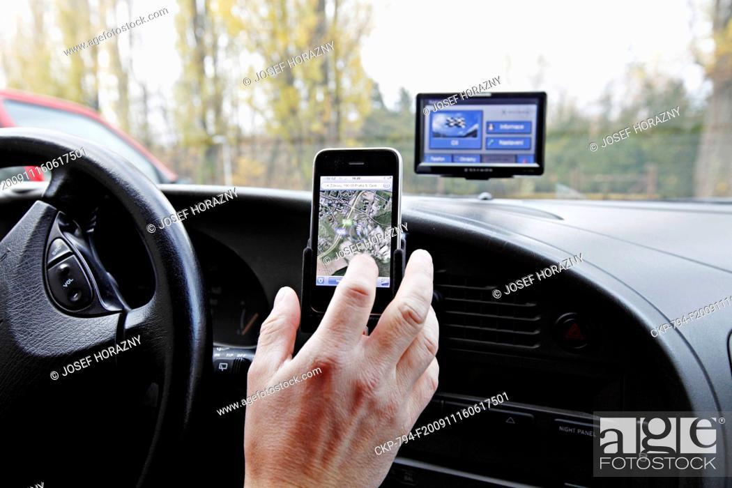 Stock Photo: Panasonic Strada GPS navigation and iPhone in a car.