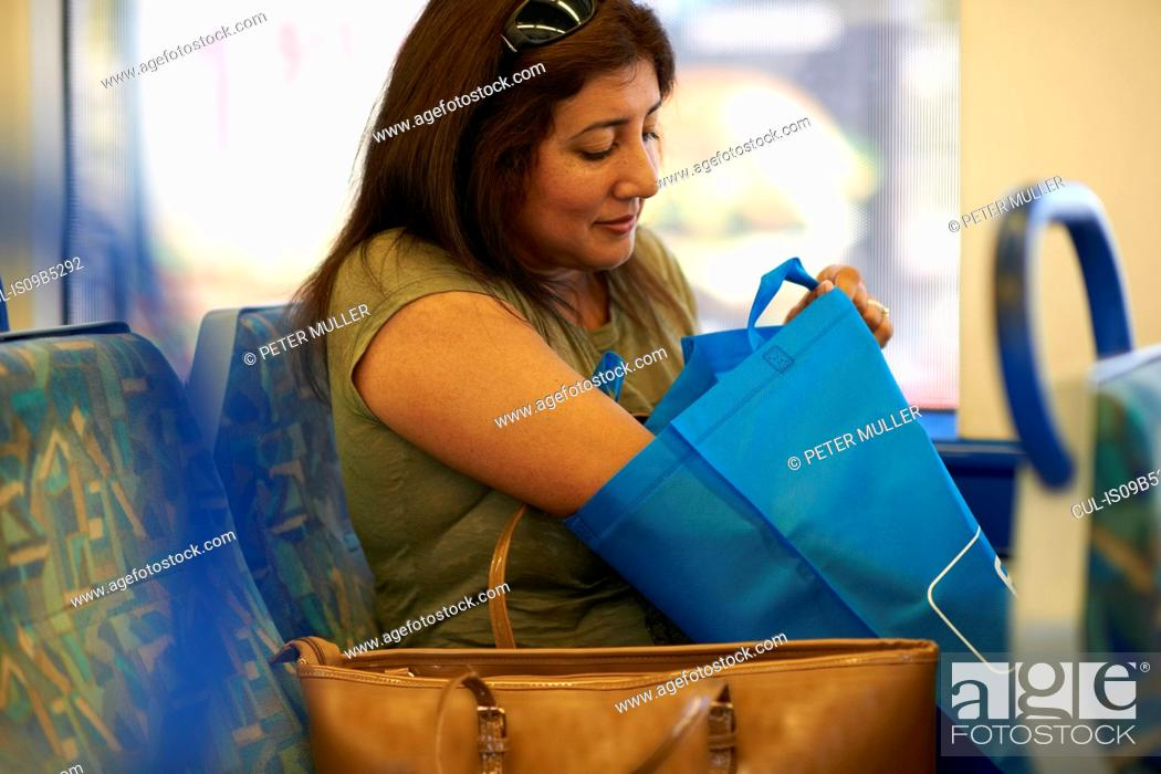 Stock Photo: Mature woman searching shopping bag in train carriage.