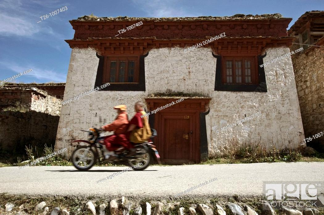 Stock Photo: Two monks Lama ride a motobike in the monastery.