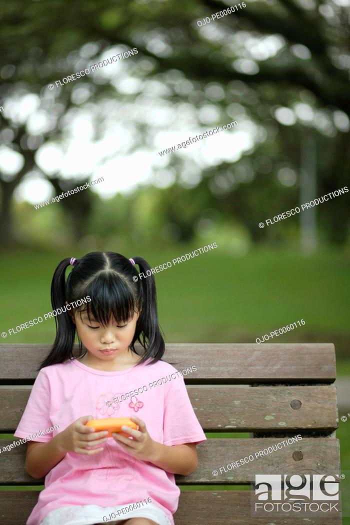 Stock Photo: Young girl outdoors on bench with video game.