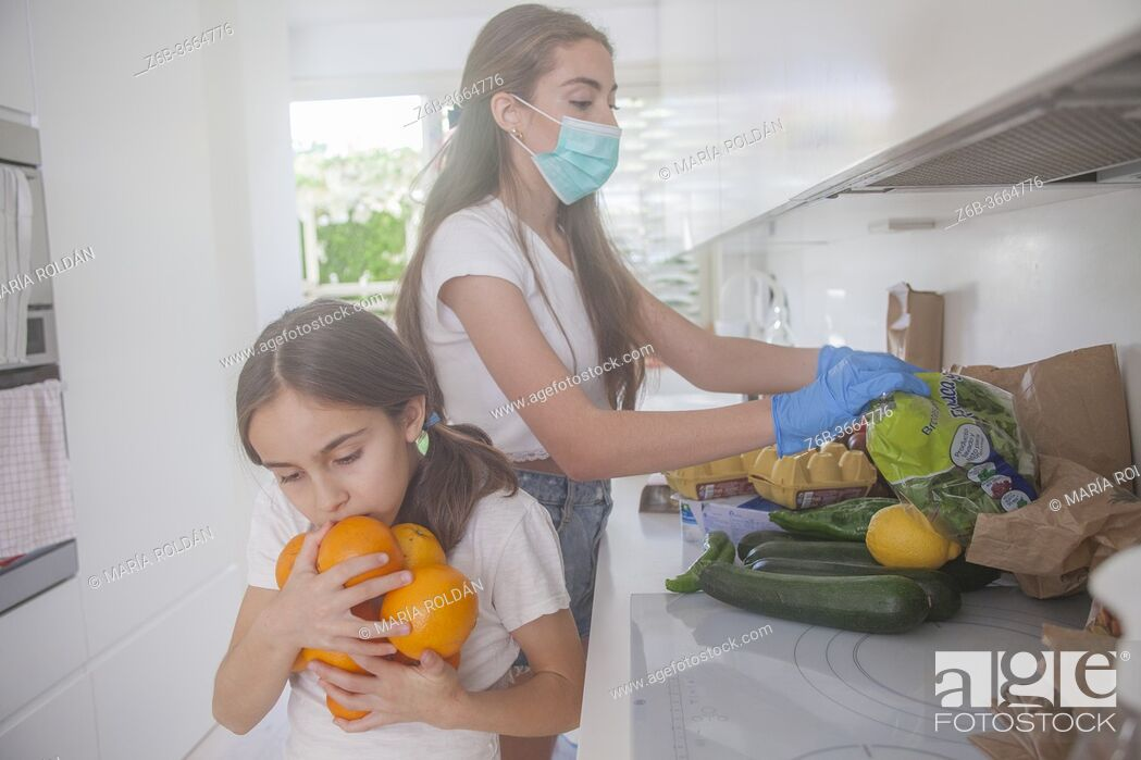 Stock Photo: Mother and child in kitchen, the mom wears a mask and gloves.