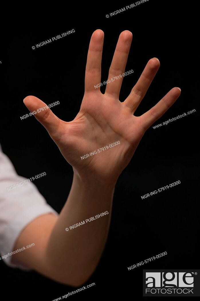Stock Photo: Female hand is showing five fingers isolated on black background.