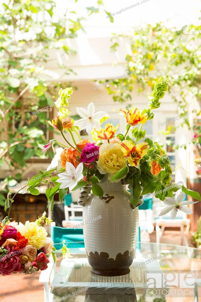 Stock Photo: Bouquet of flowers in vase on backyard patio.