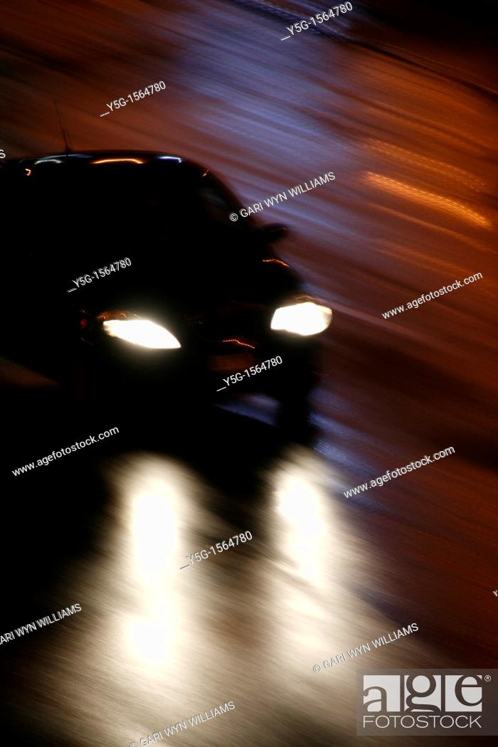 Stock Photo: fast car driving in heavy rain at night in town.