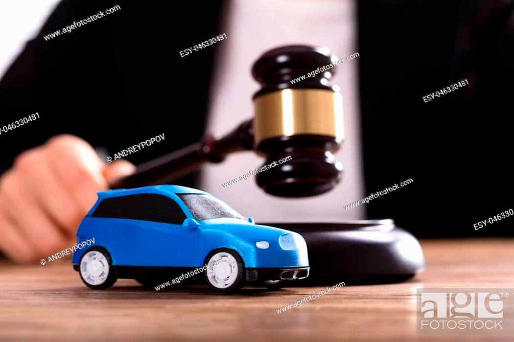 Stock Photo: Close-up Of A Small Blue Car In Front Of Judge Holding Mallet.