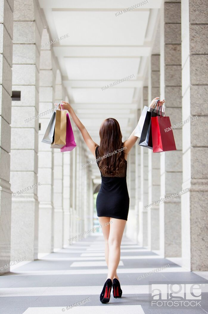 Stock Photo: Young woman standing and holding shopping bags with rear view,.