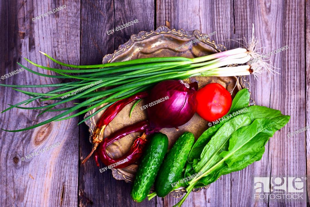 Stock Photo: Fresh vegetables on an iron copper plate, cucumber, tomato and green onions, top view.