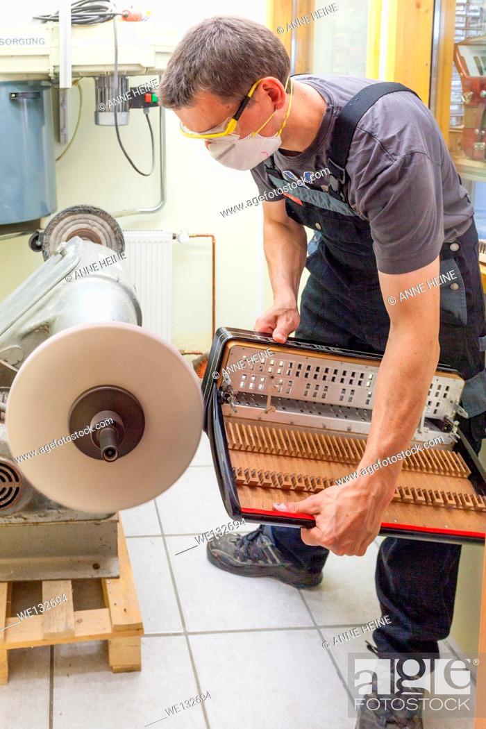 Imagen: Instrument maker polishing part of accordion at buffing machine.