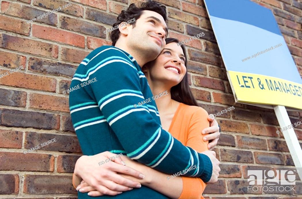 Stock Photo: Couple hugging outside house.