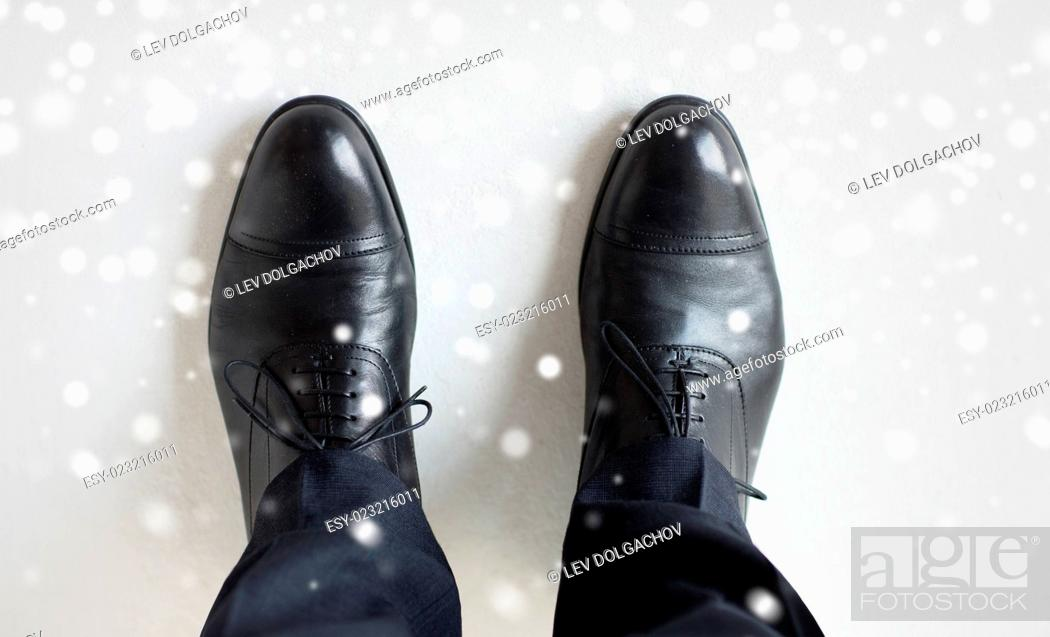 Stock Photo: people, business, fashion and footwear concept - close up of man legs in elegant shoes with laces or lace boots over snow effect.