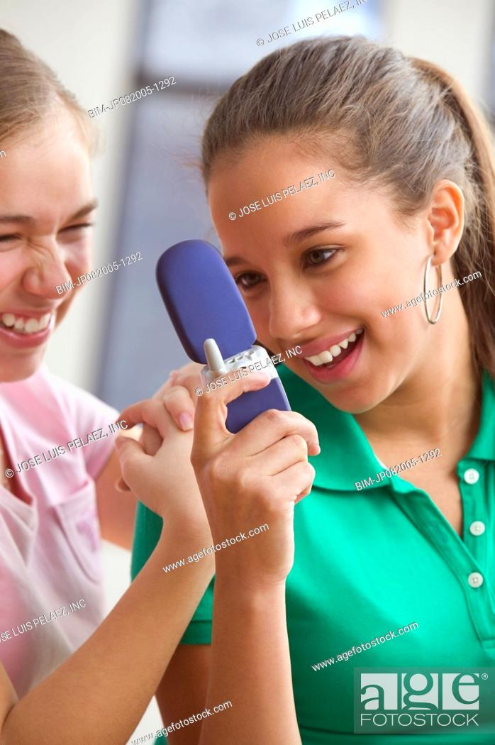 Stock Photo: Two teenage girls text messaging on cell phone.