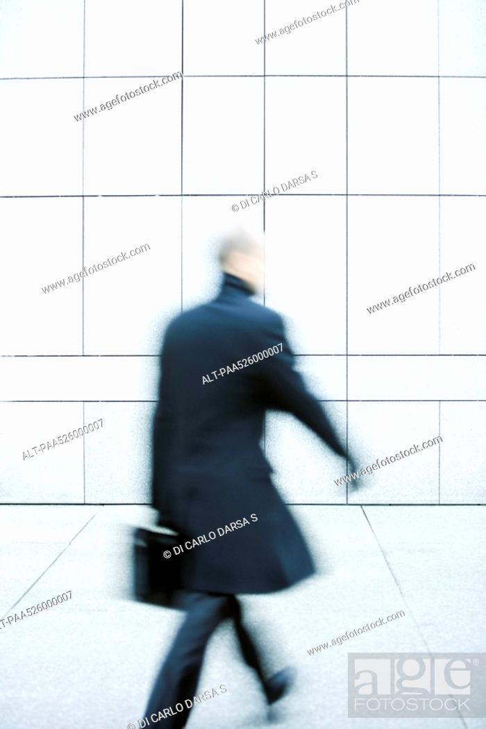 Stock Photo: Businessman hurrying down sidewalk.