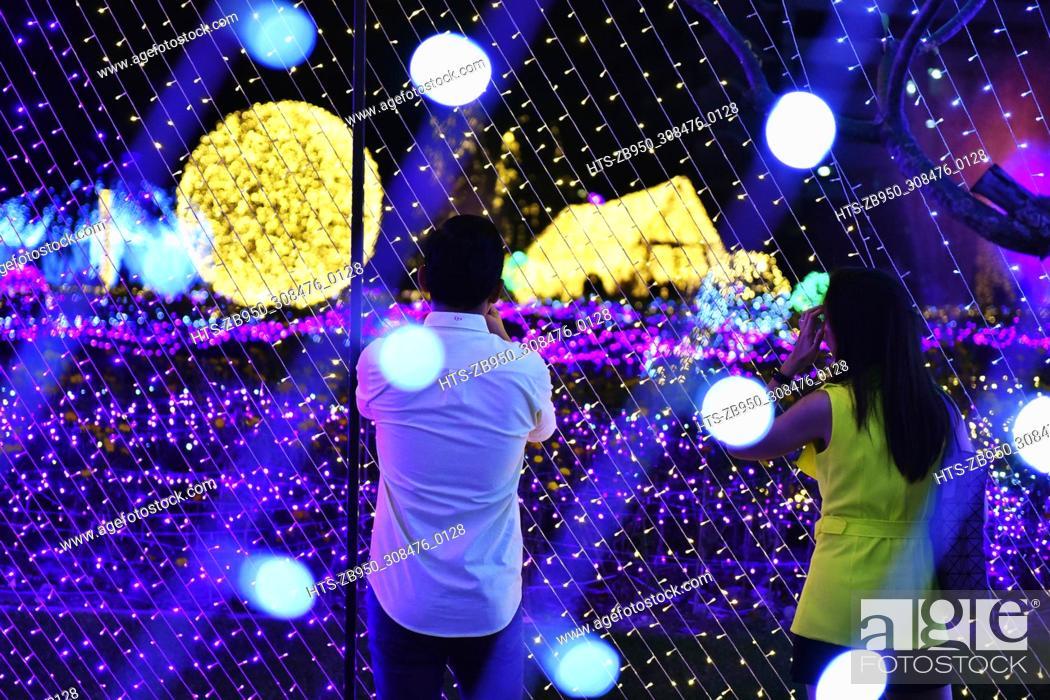 Stock Photo: (171205) -- BANGKOK, Dec. 5, 2017 () -- Two visitors look at LED art installations during Thailand Illumination Festival 2017 in Bangkok, Thailand, Dec.