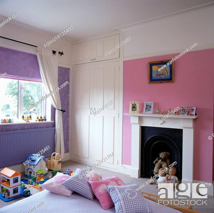 Pink and mauve child\'s bedroom with white fireplace, Stock ...