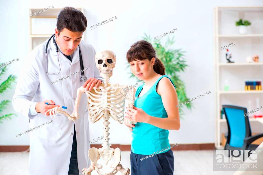 Stock Photo: Doctor showing type of injury on skeleton to patient.