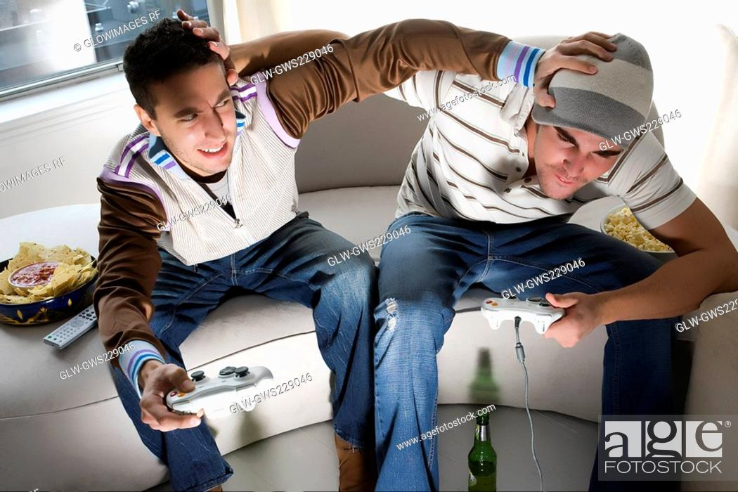 Stock Photo: High angle view of two young men playing video game and rough housing.