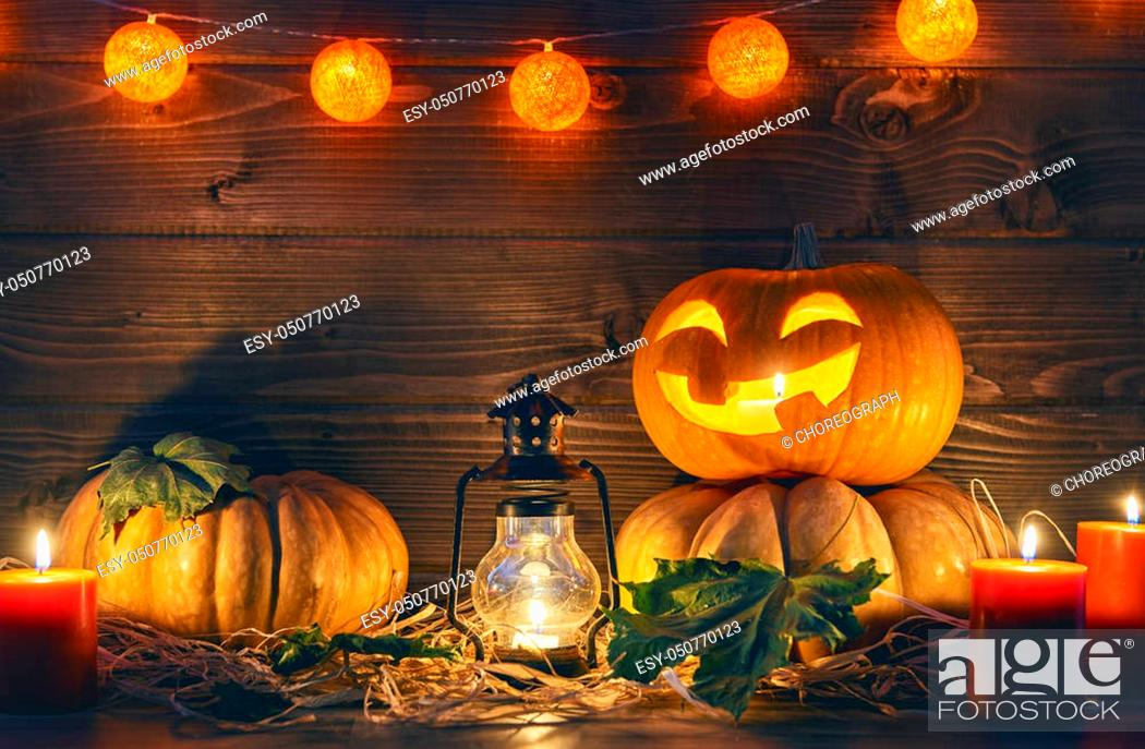 Stock Photo: Happy halloween! Head pumpkin, candles and autumn leaves on wooden background.