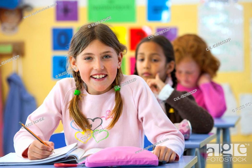 Stock Photo: Portrait of primary schoolgirl writing in classroom.