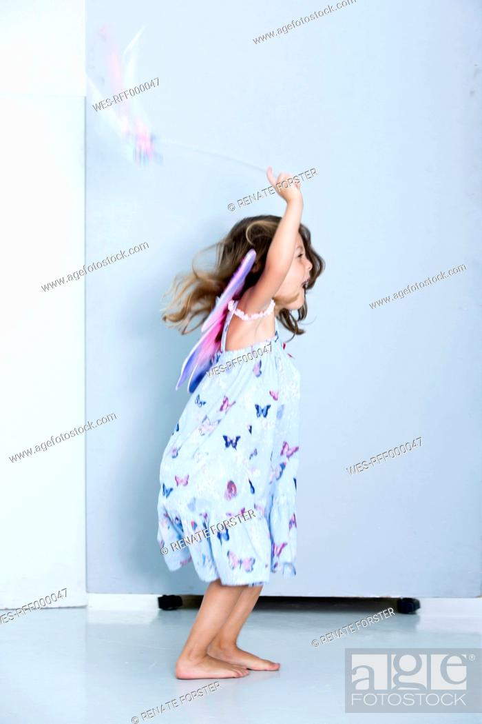 Stock Photo: Germany, Girl playing with wings.