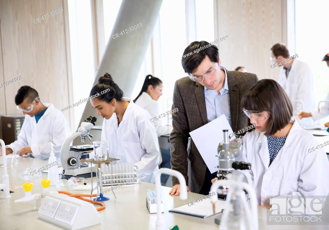 Stock Photo: Science professor helping college student conducting scientific experiment in science laboratory classroom.