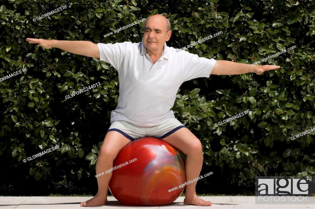 Stock Photo: Senior man exercising with a fitness ball.
