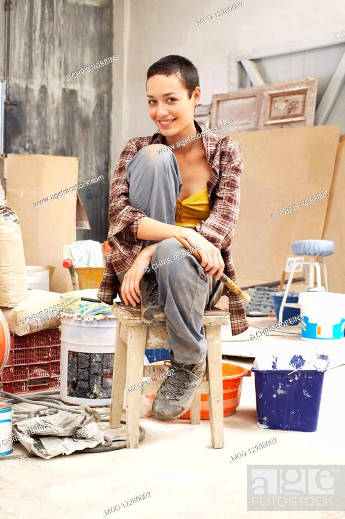 Stock Photo: Young female Painter sitting in work site with equipment portrait.