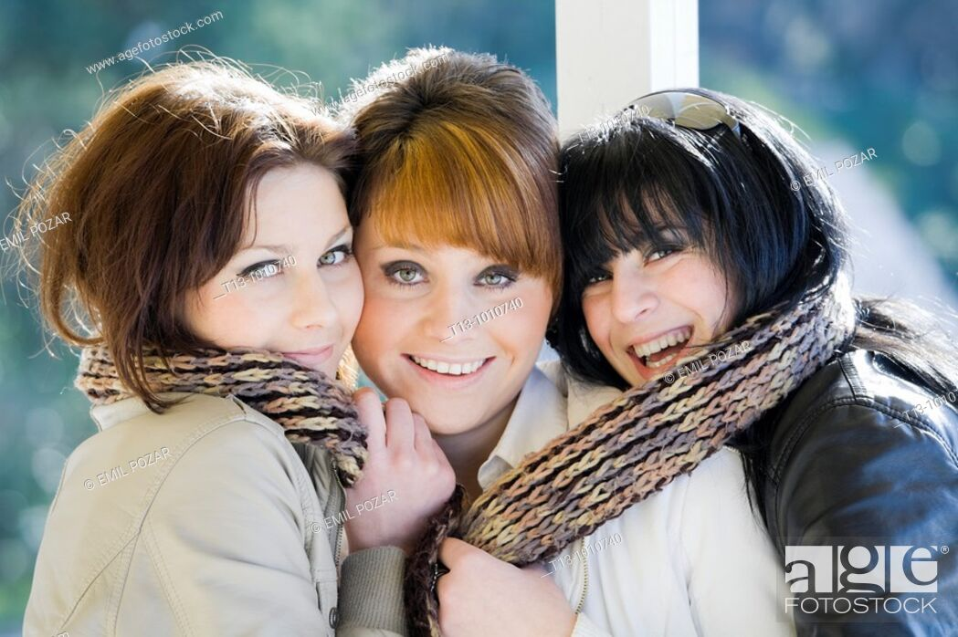 Stock Photo: Three happy girlfriends close together with just one scarf.
