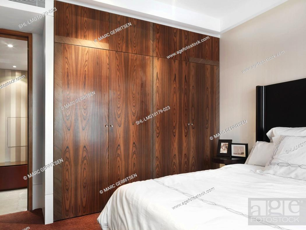 Stock Photo: White bed and wooden closet in bedroom.