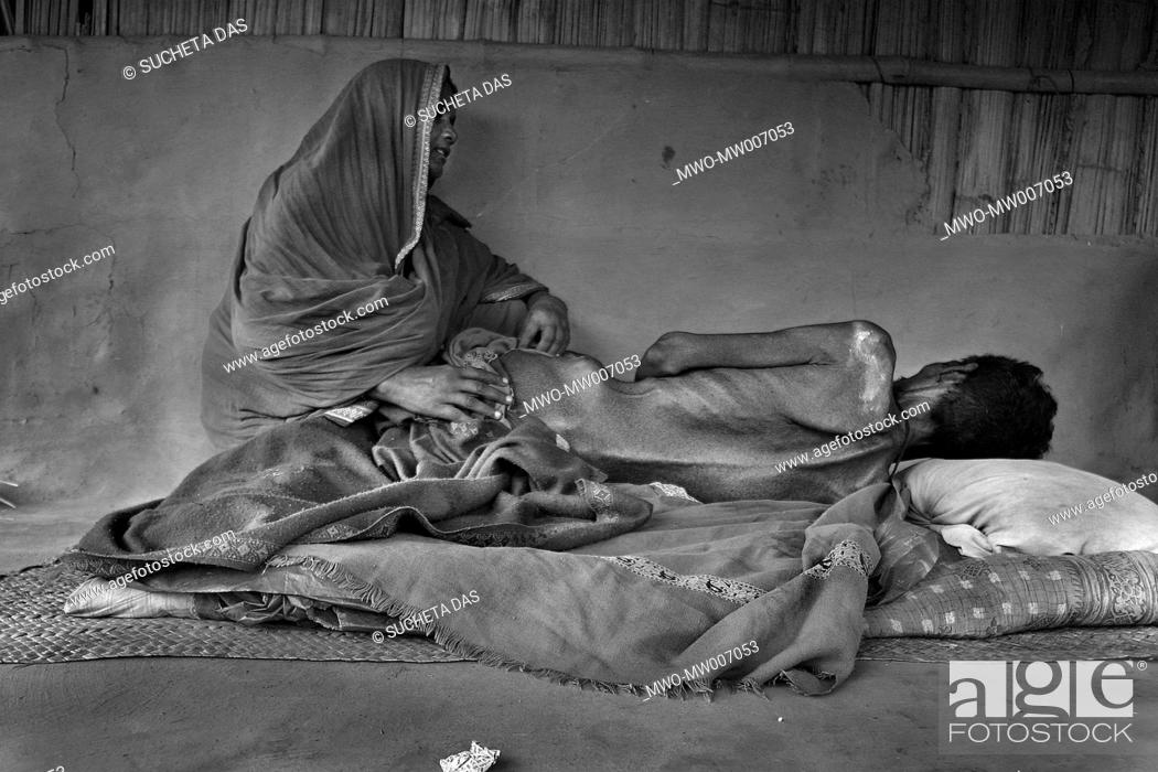 Stock Photo: Hifot Mondol, R, 50, lies on the floor, who is caused by drinking arsenic-contaminated water and his wife Khatojan Bibi sits beside him at Kadamtala village in.