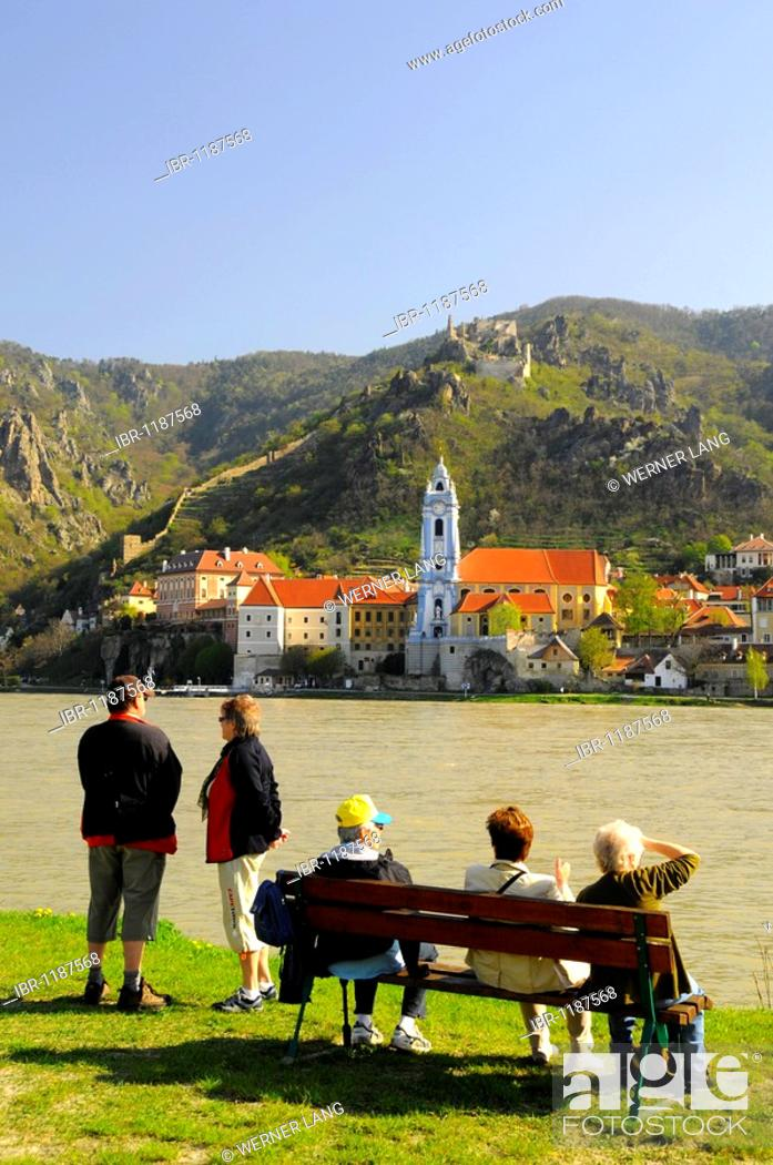 Stock Photo: Tourists and pensioners on park benches overlooking the Danube River towards the town and castle ruins of Duernstein, Wachau, Lower Austria, Austria, Europe.