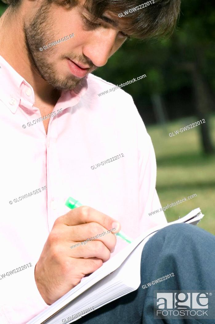 Stock Photo: Close-up of a young man writing with a pen in a notepad.